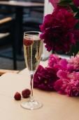 Glas Sekt mit Kirsche, Sommergetränk, rosa Pfingstrosenblüten auf dem Tisch