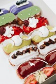 Fotografie Set of delicious eclairs with glaze, colorful dessert