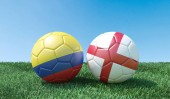 Two soccer balls in flags colours on green grass. Colombia and England. 3d image