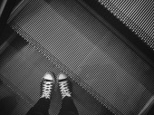 Fotografie Selfie of sneakers and escalator black and white