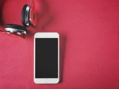 Headphones and smartphone on pink background