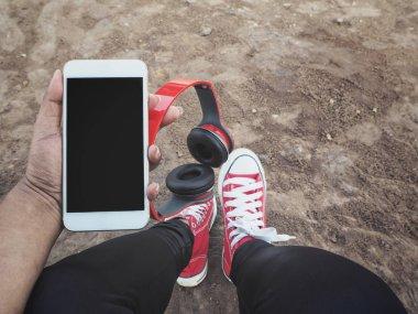 Selfie of headphones with smartphone and sneakers
