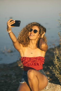 Pretty blond woman with sunglasses and mobile phone.