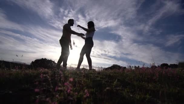 Backlight man and woman dancing at sunset.