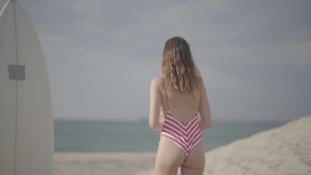 Pretty girl in a swimsuit with red stripes and surfboard.