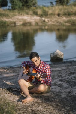 Man plays guitar by the lake