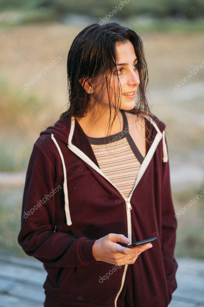 Pretty girl poses with mobile phone sunset.