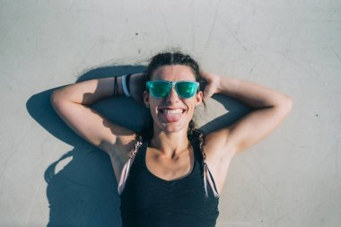 Brunette woman with sunglasses poses at camera.