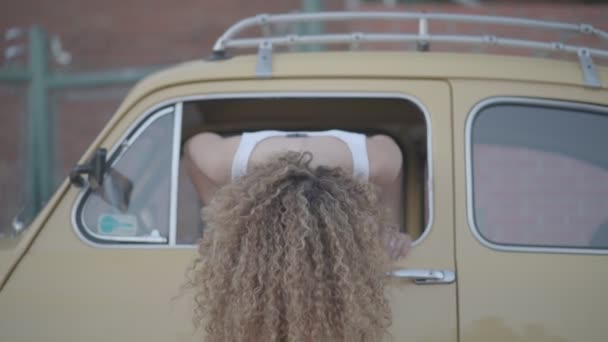 Beautiful blonde woman poses to camera in classic car.