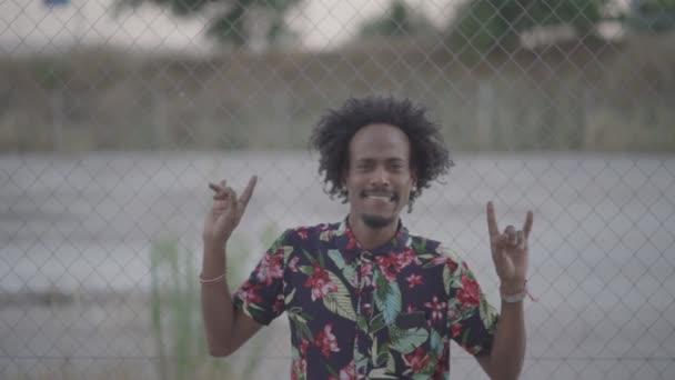 Funny African-American man dances posing at camera.