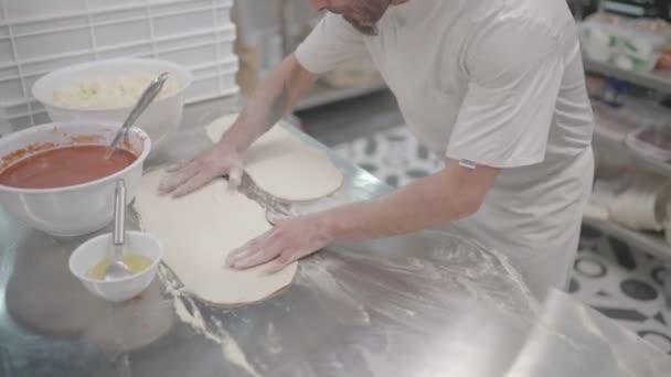 Mužské kuchař připravující pizzu v peci.