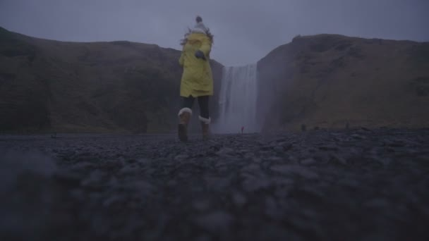 A person with yellow raincoat next to the waterfall in Iceland.