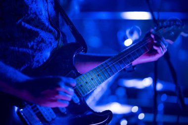 Guitarist playing with musical group in nightclub.