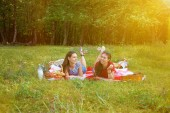 Two beautiful girls rest on a picnic in the forest Sunny day Copy space
