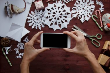 New Year's concept. A woman is making a photo for a blog. Women's hands hold a smartphone, photograph snowflakes cut from paper, gifts, scissors on a wooden table