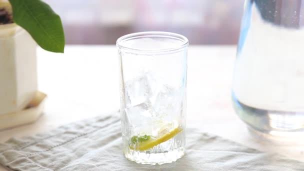 Főzés és öntés egy pohár vizet citrommal, a jég és a menta