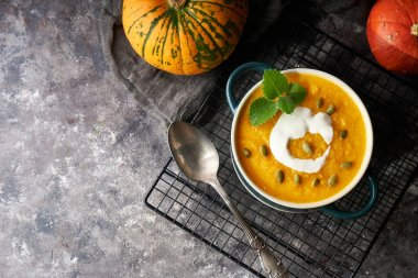 Traditional pumpkin soup puree with cream and seeds in a bowl, on a dark background Copy space