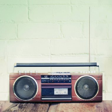 Retro radio player with buttons and antenna on white wall background