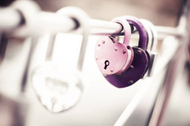 closeup view of love locks on bridge, blurred background