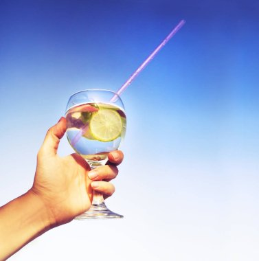 cropped image of hand holding lemonade in glass with straw