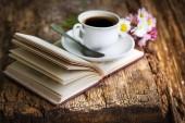 Vértes nézet a virágok és a fából készült asztal könyv csésze kávé