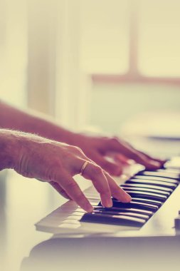 Male hands pressing on piano buttons
