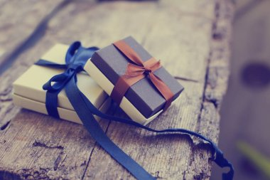 Colorful gift boxes with ribbons on wooden background