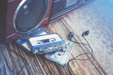 headphones with cassettes and recorder on wooden background