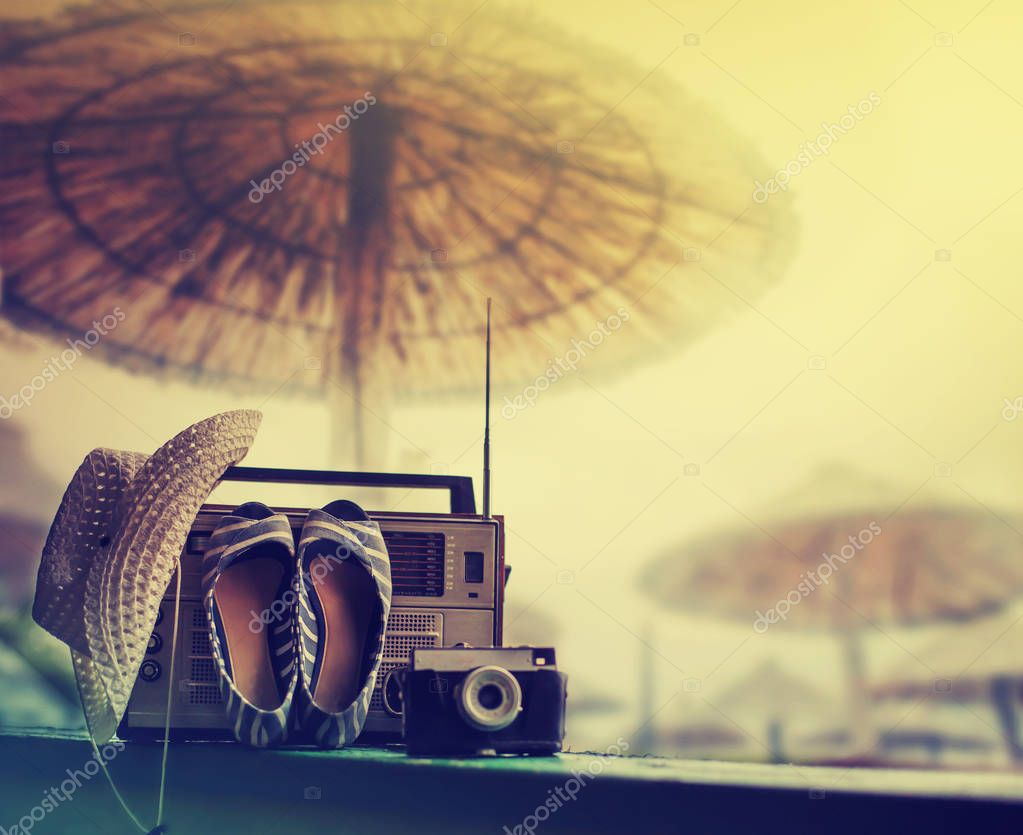 Retro radio player with hat and shoes against nature background