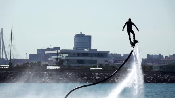 Silueta muže baví na Flyboard s Valencií v pozadí