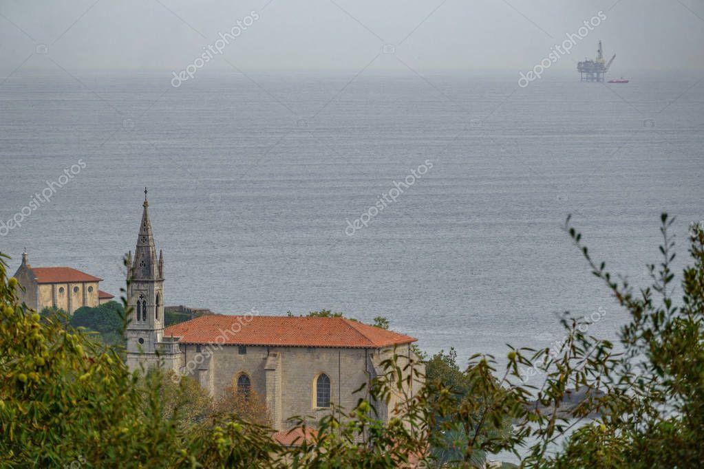 Mundaka church with gas ocean platform in the horizon