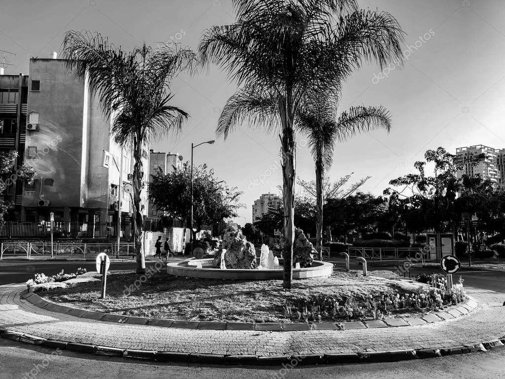RISHON LE ZION, ISRAEL -APRIL 23, 2018: Roundabout with small fountain on the street with palms in Rishon Le Zion, Israel.