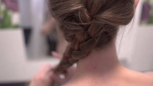 Frau flechtet ihre Haare im Badezimmer. 4k uhd Nahaufnahme.
