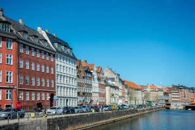 COPENHAGEN, DENMARK - MAY 5, 2018: Urban scene with city river, blue sky and colorful buildings in copenhagen, denmark stock vector