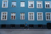 boční pohled na mladou ženu, chůze v blízkosti modrého domu s velkými okny v Kodani, Dánsko