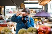 Fotografie žena s tváří zakrytou fotoaparátem vyfotit v obchodě