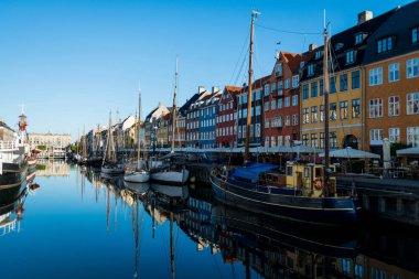 COPENHAGEN, DENMARK - 06 MAY, 2018: Nyhavn pier with buildings and boats reflected in water, Copenhagen, Denmark stock vector