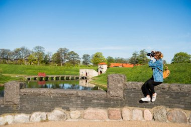 young woman with camera sitting on stone fence and photographing Citadel, copenhagen, denmark