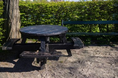 empty round wooden table with benches in park, copenhagen, denmark