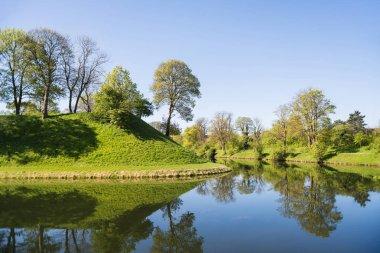 beautiful green hills, trees and bushes reflected in water, copenhagen, denmark