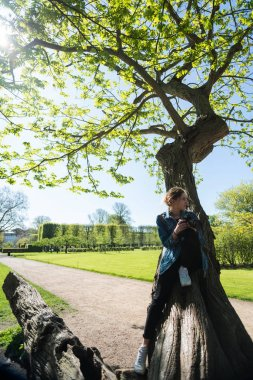 beautiful girl with camera sitting on tree and photographing in green park, copenhagen, denmark