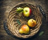 Čerstvá jablka a hrušky v proutěný podnos, pohled shora