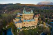 Letecký pohled na Bojnický zámek na Slovensku střežený příkopem a obklopený lesy.