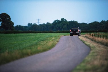 Pickup truck driving on country road in evening