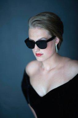Retro 1950s woman in black dress and sunglasses.