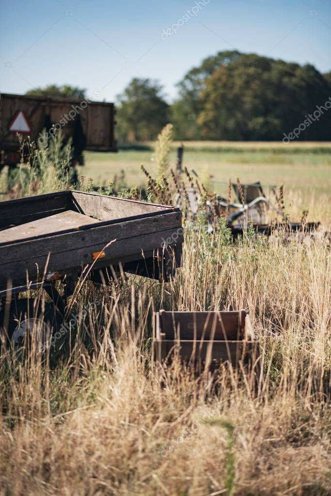 Old neglected trailer in farmland on sunny summer day.