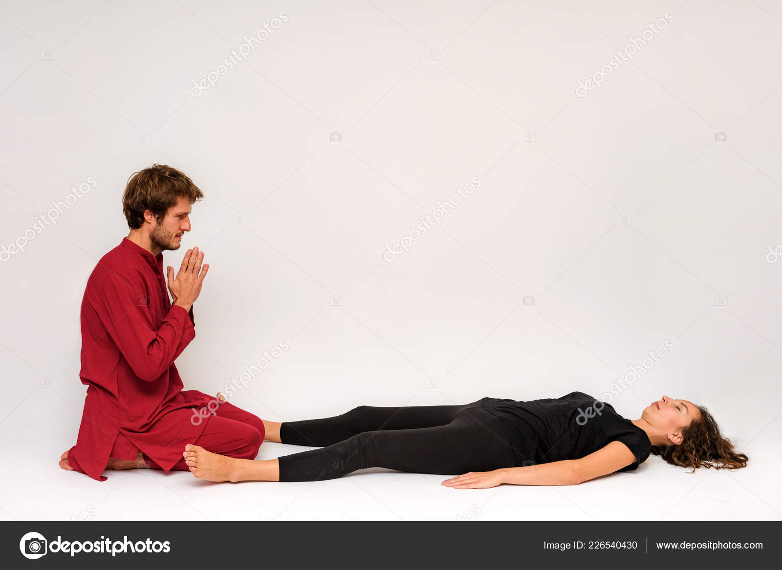 Photo of yoga poses on the floor for two stretching and relaxing on a white  background. The man stretches the woman right in front of the camera.