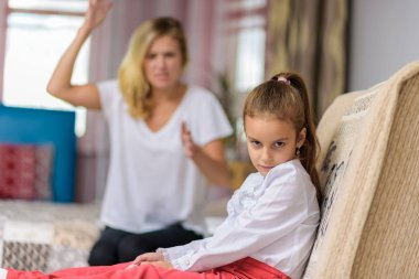 Family conflict, family relationship mother and child daughter. Mom scolds an angry daughter who sits on the sofa