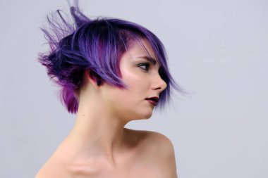 A beautiful, sexy girl with purple hair and a short haircut sits in the middle of the photo with a white background and grimaces. She's naked and visible shoulders.