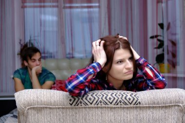 Family problems, family relationships of the disgruntled husband and wife in the room speak, swear on the sofa. They are directly in front of the camera in different poses.